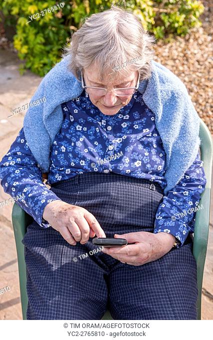 A woman in her 80's using a smart phone in the Uk