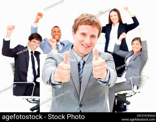 Happy ma ger with thumbs up in front of his team