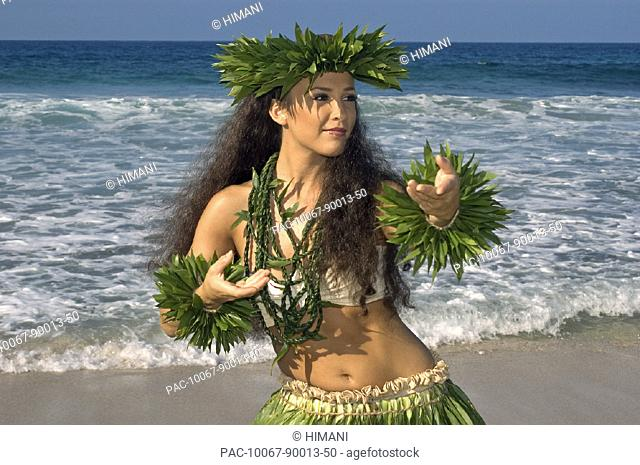 Hula dancer in ti-leaf skirt, haku, lei, in a dancing pose on the beach