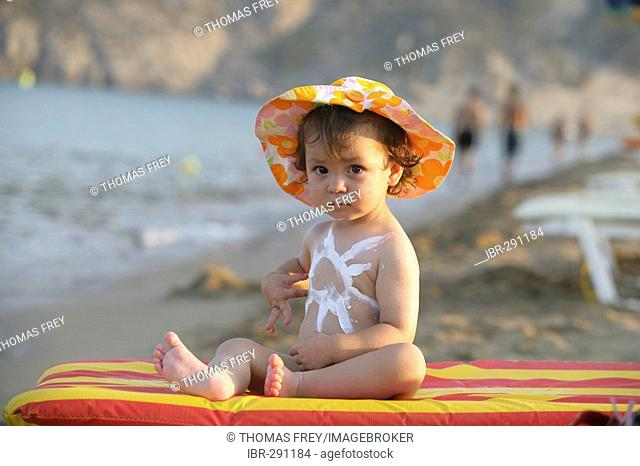 Baby with sun lotion and sun shade