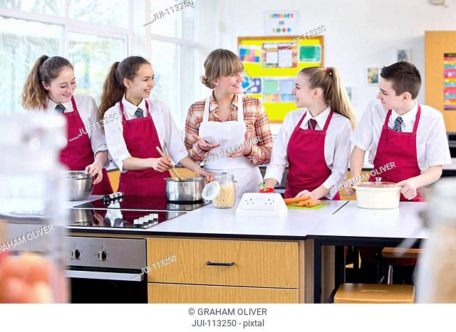 Teacher guiding high school students cooking in home economics class
