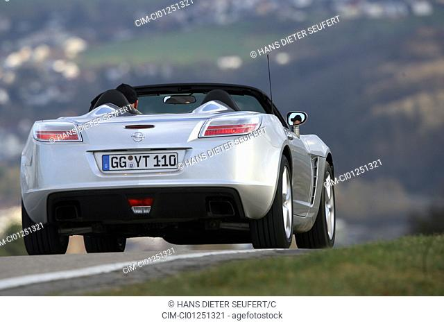 Opel GT, model year 2007-, silver, driving, diagonal from the back, rear view, country road, open top