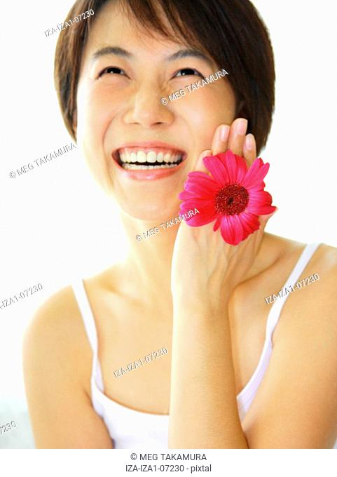 Close-up of a young woman with a Gerbera Daisy holding between her fingers