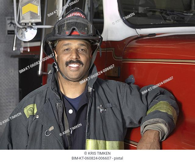 African male firefighter leaning against fire truck
