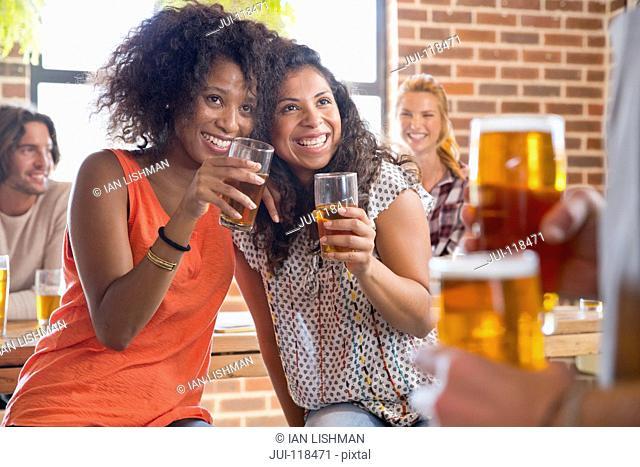 Flirtatious Female Customers Toasting Waiter In Bar