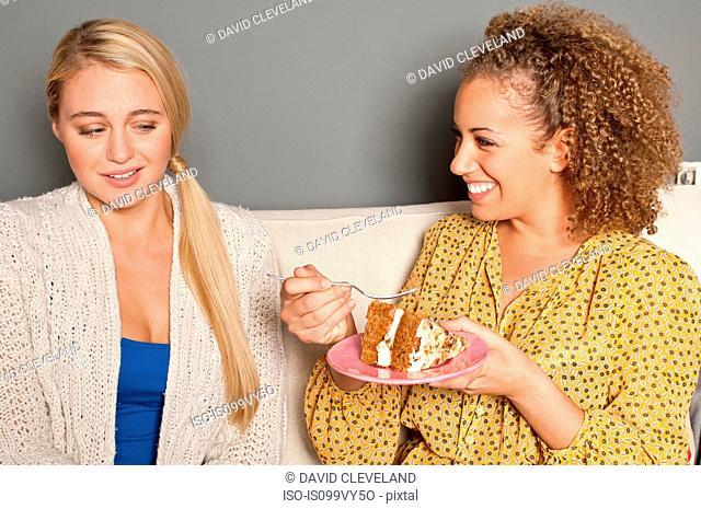 Woman staring at friend eating cake
