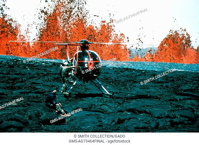 Several Hawaiian Volcano Observatory geologists board a helicopter while lava fountains from Mauna Loa erupt in the background, Hawaii, 1984