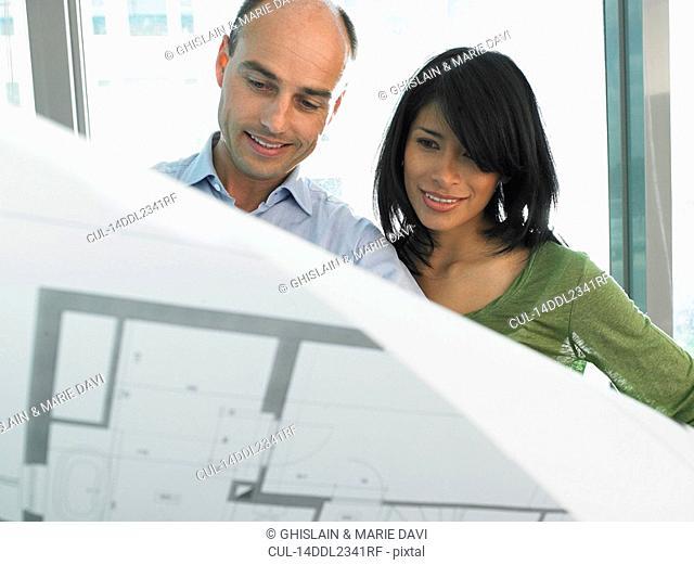 Man and woman looking at blue prints