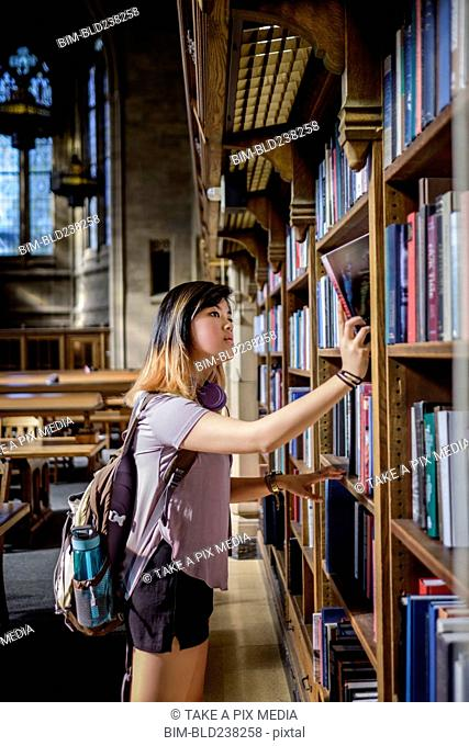 Chinese woman standing in library choosing book