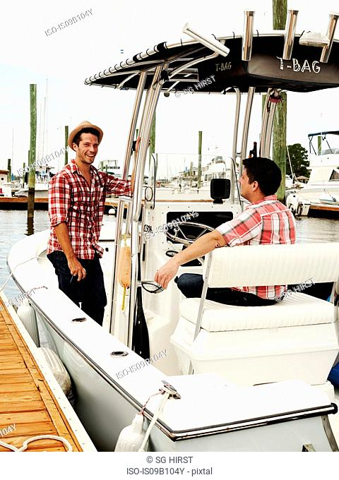 Two adult brothers talking on motorboat in marina