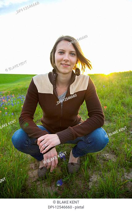 Portrait of a young woman in a meadow with wildflowers at sunset; Waco, Texas, United States of America