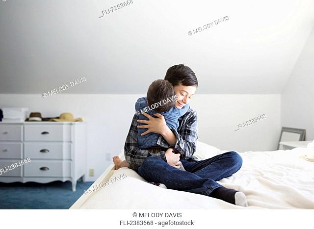 Mother on a bed hugging her down syndrome child; Victoria, Vancouver Island, British Columbia, Canada
