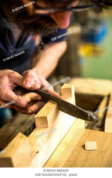 Woodworker Using Rasp on Piece of Wood, High Angle View