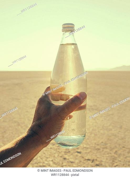 The landscape of the Black Rock Desert in Nevada. An essential element for survival. A man's hand holding a bottle of water. Filtered mineral water