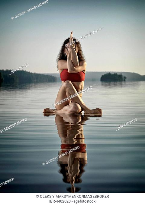 Woman doing a variation of yoga Eagle posture, Guradasana, meditating on a floating platform in water on the lake in morning light