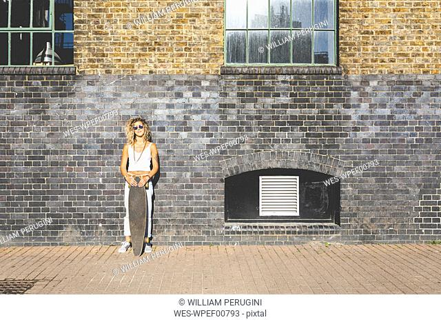 Young woman standing with skateboard at brick wall in the city