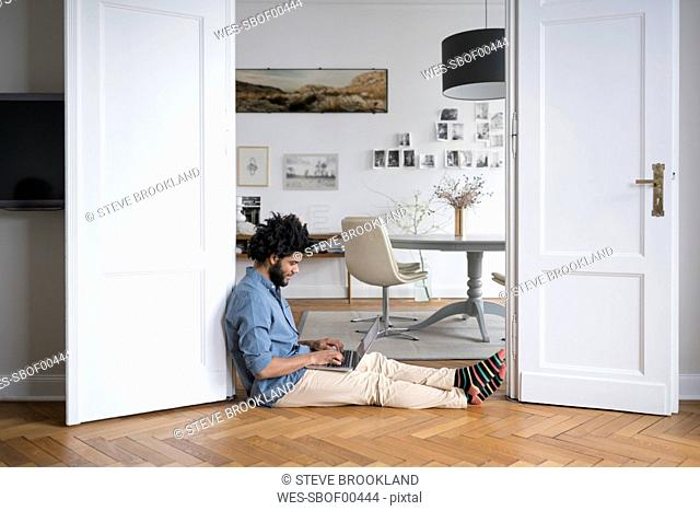 Man at home sitting on floor working with laptop in door frame