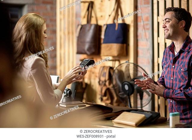 Woman paying with credit card in leather goods shop