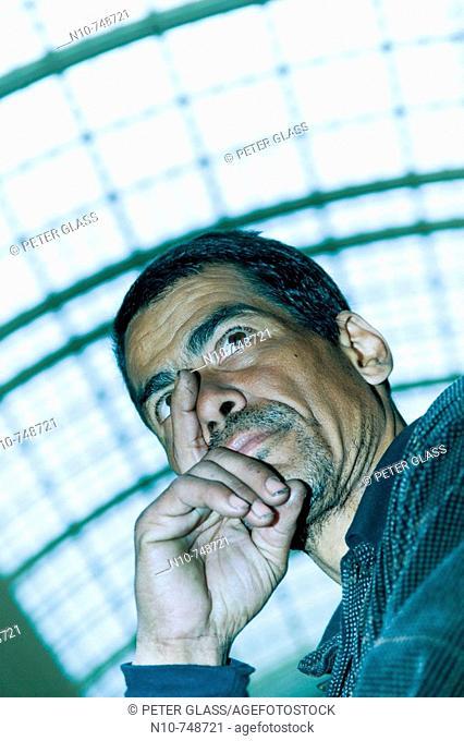 Hispanic man standing under an office building skylight