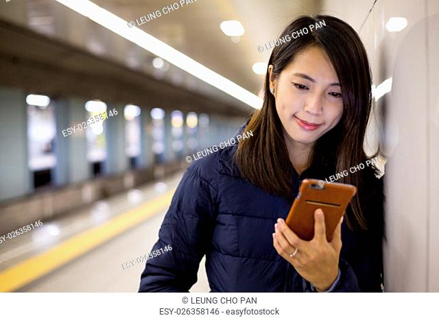 Woman use of cellphone in platform