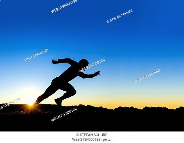 Germany, Winterbach, jogger at sunset