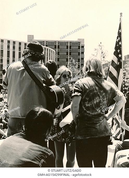 Student in hippie attire holding a guitar prepares to play for a large group, with American flag visible, during an anti Vietnam War student sit-in protest at...