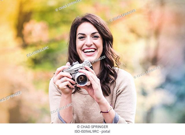 Portrait of smiling young woman using SLR camera in autumn forest