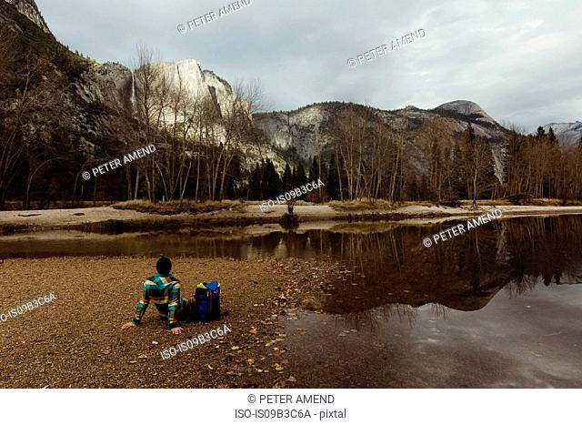 Male hiker sitting by lake looking out at landscape, Yosemite National Park, California, USA