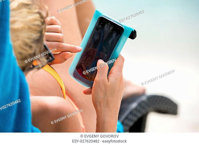 Blonde girl is lying on the sunbed and writing message
