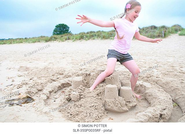 Girl destroying sand castle on beach