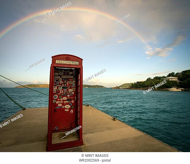 Rainbow over a red phone booth standing on a jetty by the sea