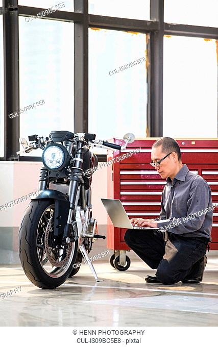 Technician in garage, checking electric cafe racer motorbike on diagnostic computer