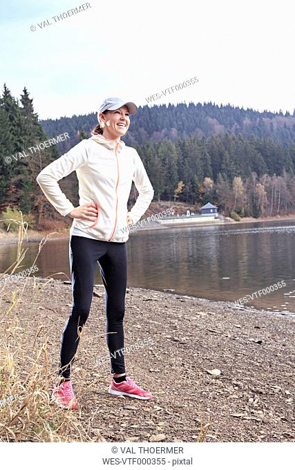 Smiling female jogger with hands in her hips standing at lakeshore