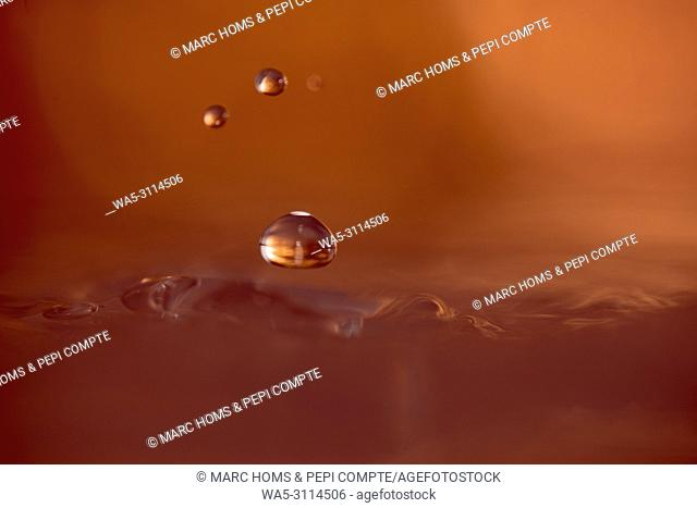 Three drops of copper-colored water suspended above the surface of the water