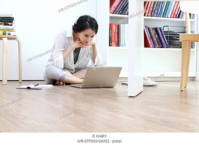 A young woman sitting with a laptop computer