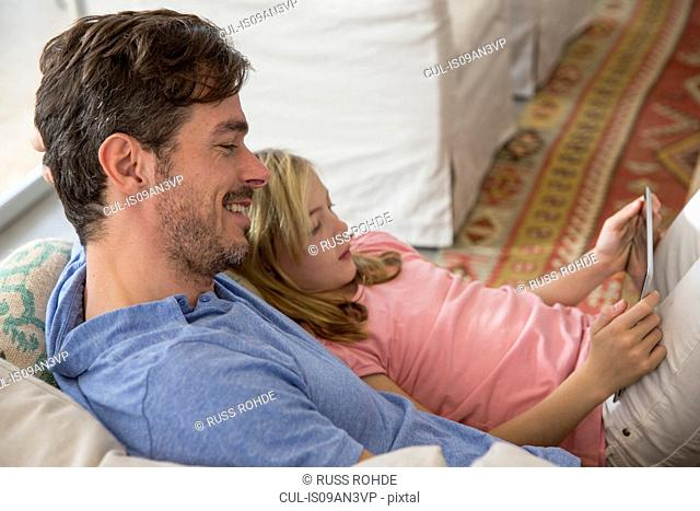 Mature man and daughter reclining on sofa using digital tablet