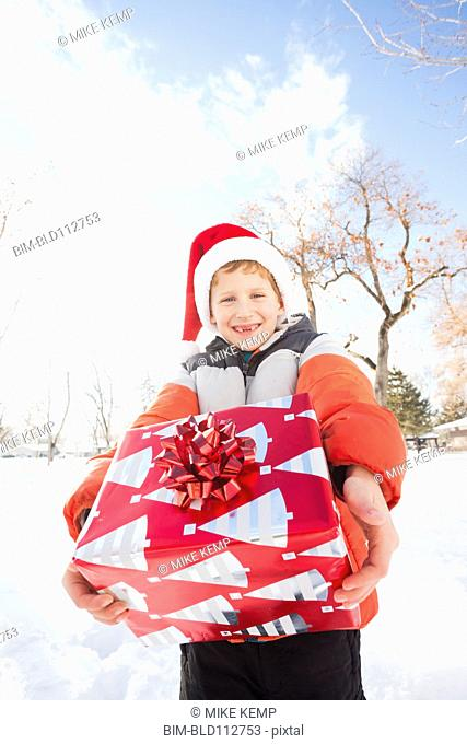 Caucasian boy in Santa hat holding Christmas present