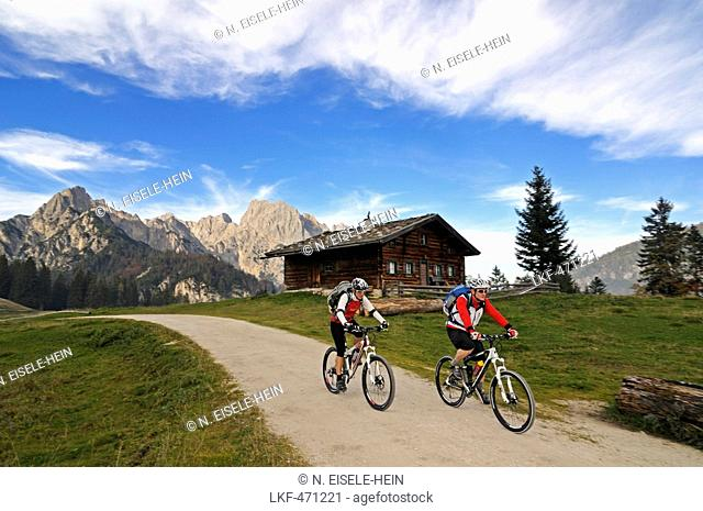 Mountain bikers passing Litzlalm, mount Hochkalter in background, Berchtesgadener Land, Upper Bavaria, Germany