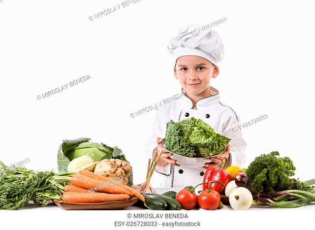 One little boy as chef cook making salad, cooking with vegetables. Isolated on white