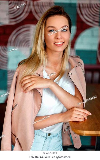 Funny young model woman with a smile in a pink jacket and denim shorts sitting on a chair indoors