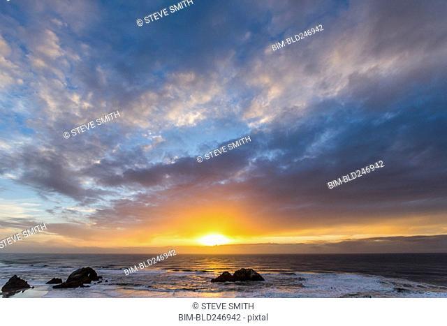 Rocks in ocean at sunset