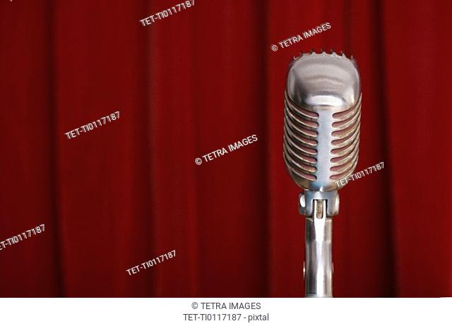 Old fashioned microphone with red curtain