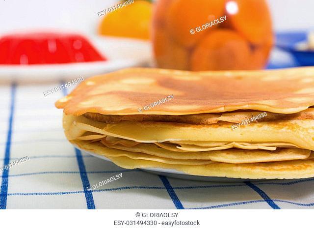 Tasty pancakes with fruits on back background