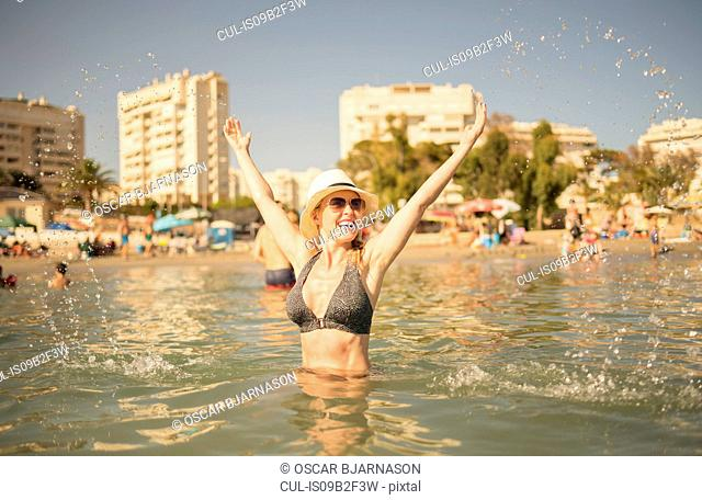 Happy woman splashing in sea, Alicante, Spain