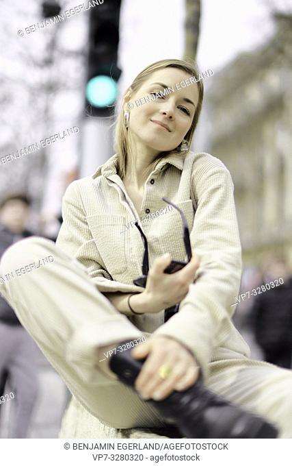fashionable woman sitting at street during fashion week, in Paris, France