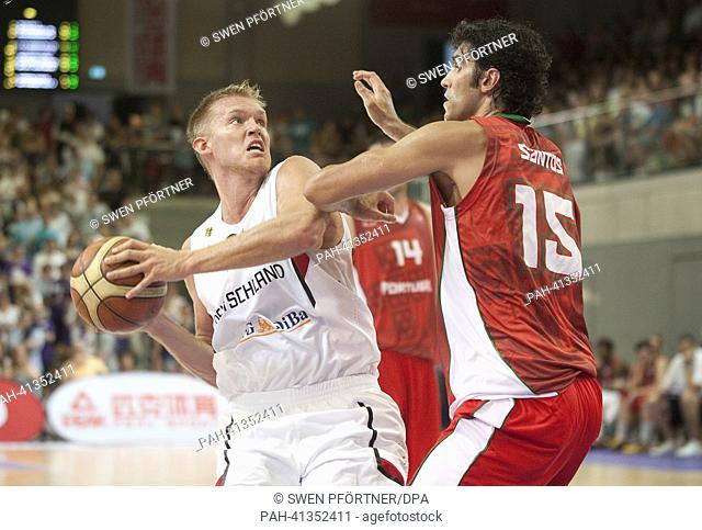 Germany's Johannes Lischka (L) plays against Portugal's Joao Santos during the international basketball match Germany vs