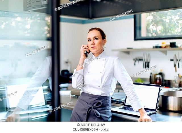 Chef using cellphone in kitchen