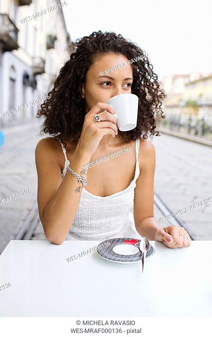 Young woman drinking coffee at sidewalk cafe