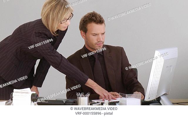 Two associates discussing over a desktop