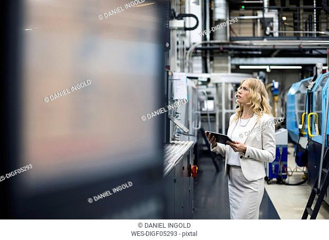 Woman with tablet at machine in factory shop floor looking around